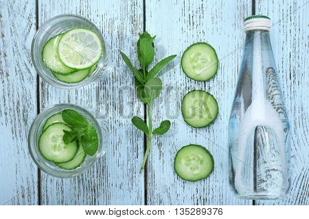 Infused lime water with mint and cucumber on wooden background