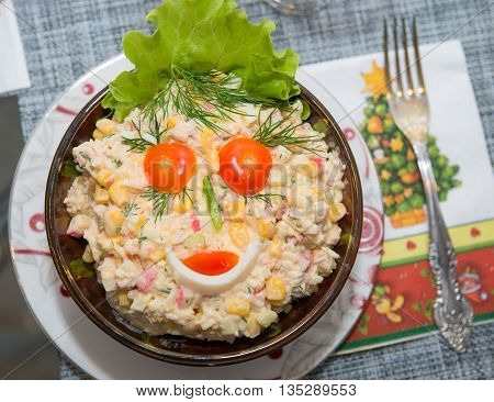 Food background - salad olivier close-up. Green peas cucumber potatoes sausage mayonnaise. Decoration in the form of a face from tomatoes