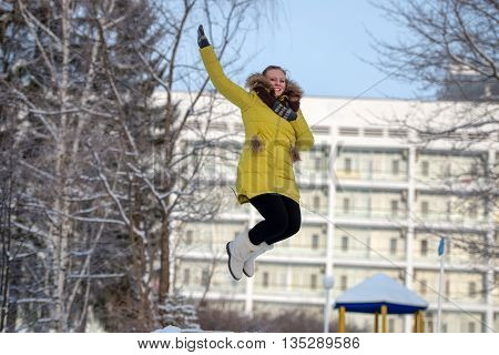 Happy girl jumps high in the winter