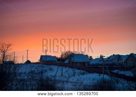 Winter bright sunset late in the evening in the village