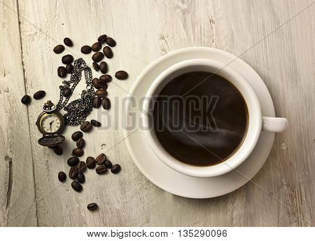 A cup of black coffee with a whiff of steam with coffee beans and a vintage chain watch shot from above on a wooden board texture slightly toned in sepia; coffee time concept