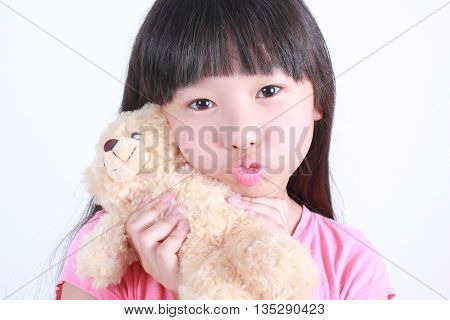 Girl with Teddy-bear in an embrace on white background.