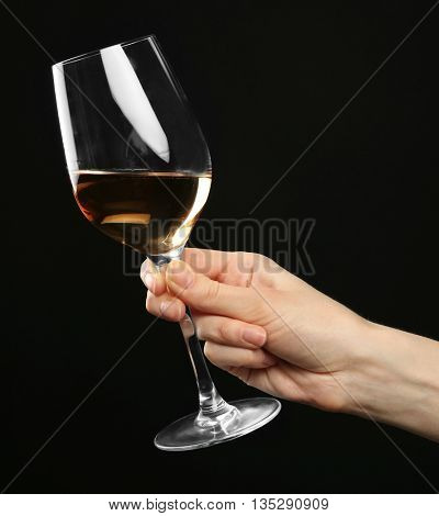 Female hand holding glass of champagne on black background