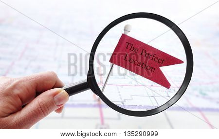 Hand with magnifying glass over a Perfect Location pin flag on a map