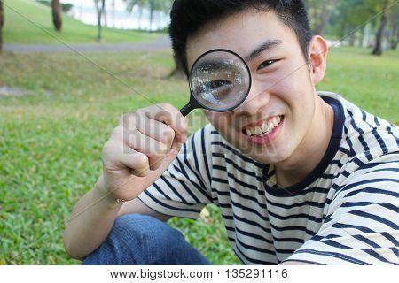 Young man with magnify glass, in the park, spring time.