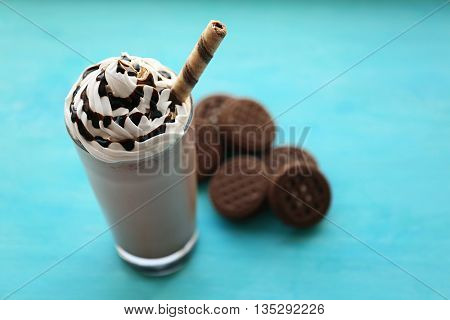 Delicious milkshake with cookies on wooden table