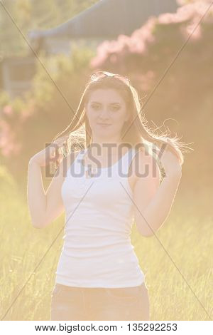 Young beautiful girl posing outdoors at nature. Lovely summer sunset backlight