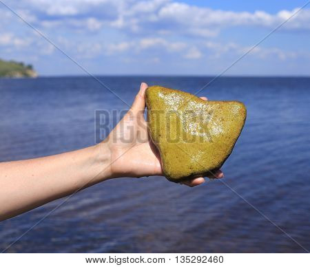woman holding in the hands of stone-like heart. against the background of the river