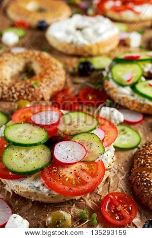 Delicious Bagel sandwiches with soft cheese, chorizo and vegetables.