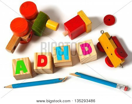Broken toys and wooden blocks with letters ADHD