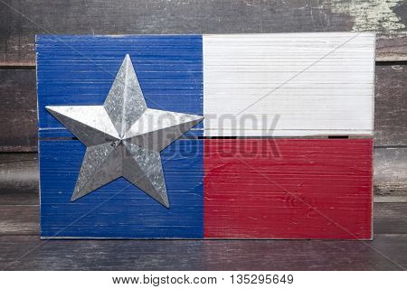 The state flag of Texas against a wood background