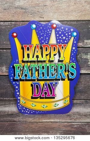 A happy father's day sign against a wood background