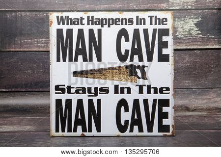 A novelty sign for the man cave against a wood background