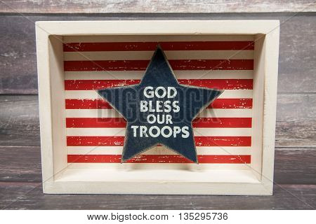 A patriotic sign saluting the military against a wood background