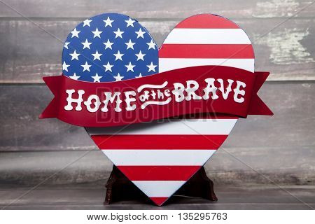 A home of the brave sign with an American flag in the shape of a heart