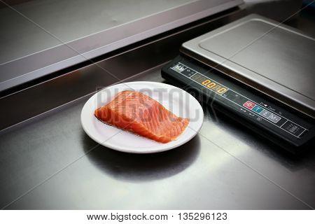 fresh salmon fillet in plate on restaurant kitchen, Libra on background
