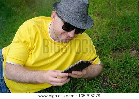 smart young man in a yellow T-shirt with the phone on the grass.