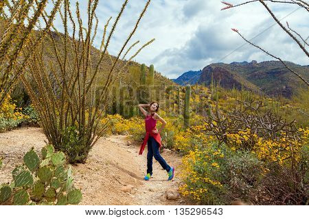 A silly tween girl poses in the Arizona desert on a cloudy day amidst saguaros ocotillos and brittle brush.
