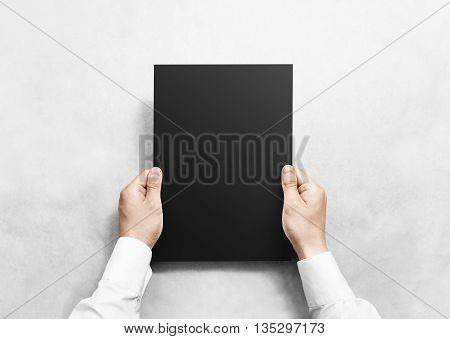 Hand holding black blank paper sheet mockup, isolated. Arm hold clear grey brochure template mock up. Leaflet document surface design. Simple pure dark print display show. Reading contract agreement.