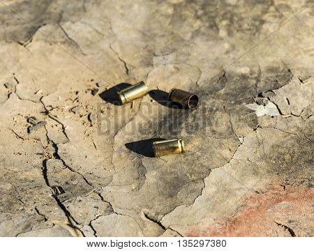 Used bullets laying down on the ground.
