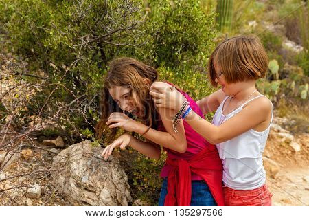 Typical sisters play fighting while laughing. One is wearing a set of play handcuffs as a bracelet. They are in the Arizona desert.