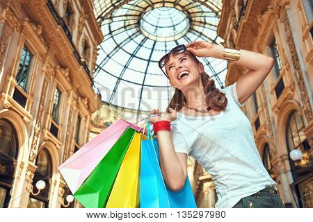 Discover most unexpected trends in Milan. Smiling fashion woman with eyeglasses and colorful shopping bags in Galleria Vittorio Emanuele II looking into the distance