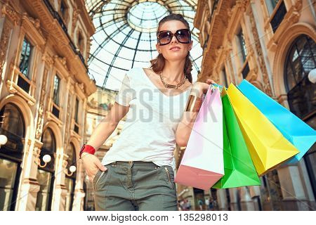 Discover most unexpected trends in Milan. Portrait of fashion woman in eyeglasses with colorful shopping bags in Galleria Vittorio Emanuele II looking into the distance