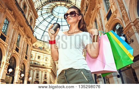 Discover most unexpected trends in Milan. Fashion woman in eyeglasses with colorful shopping bags and coffee cup in Galleria Vittorio Emanuele II looking aside