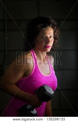 A female trainer holds a dumbbell and poses for a split light portrait.