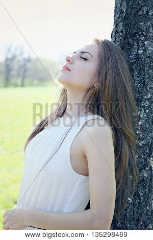 dreamy beautiful young woman near the tree