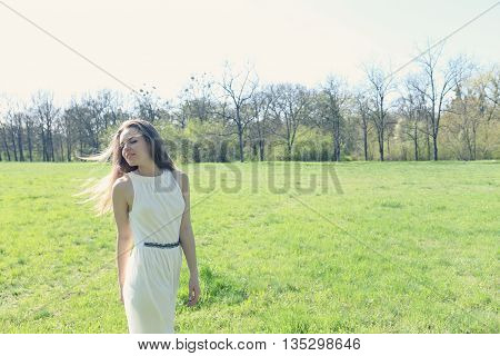 freedom dreamy girl in a summer dress in a meadow