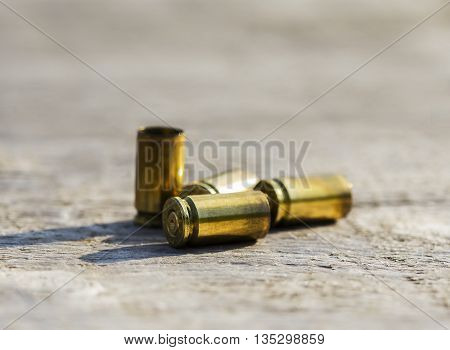 Empty bullet shells placed on a wooden table.
