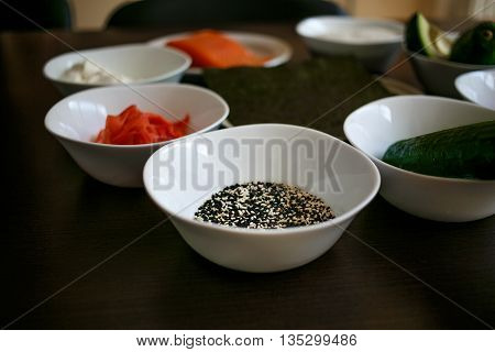 Table served with Ingredients of sushi in plates on dark background. rice with vegetables, nigiri, soy sauce, cucumber, salmon, avocado, caviar, nori . Before to be a roll. Selective focus on sesame