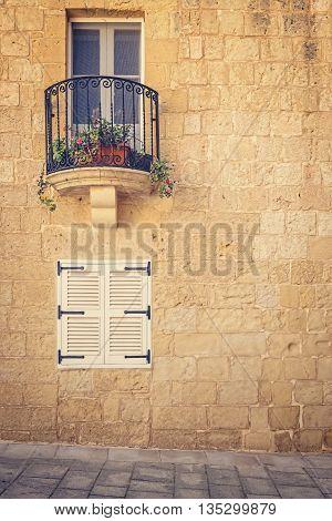 Window and balcony on old stone wall, Malta, Mdina