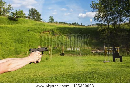 Person is holding a gun and it's aiming at a target.