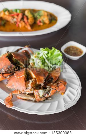 Thai Food steamed blue crabs cut in half put on white dish and wood table with spicy sauce. Selective Focus.
