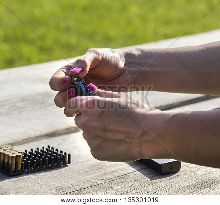 Woman is loading a clip with a bullet.
