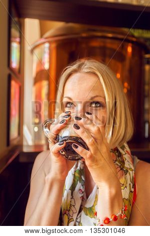 Beautiful girl drinking beer from the glass cup in bar. Girl tasting beer in brewery in Prague. Czech Republic.