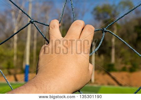 Asian man hand grab the rope mesh fence