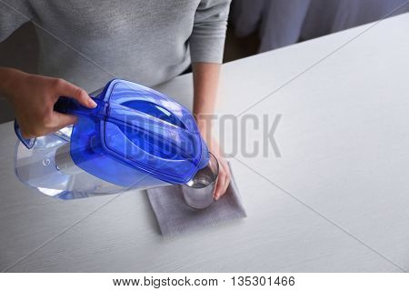Woman pouring filtered water in glass, top view
