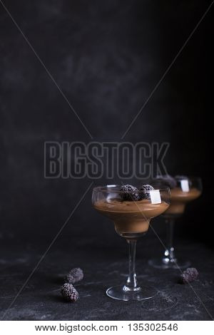 Chocolate mousse in glasses on a dark background with blackberries