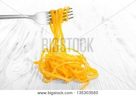 Fork with cooked pasta on white wooden background