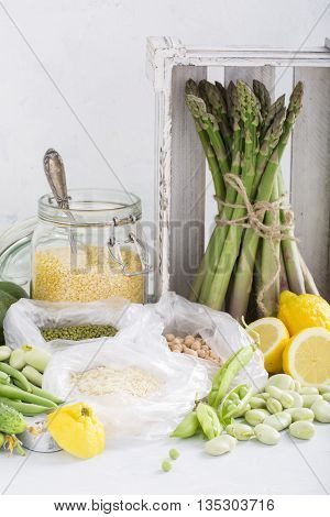 Still life of green and yellow vegetables and cereals on a light background