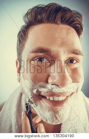 Happy smiling man shaving using razor with cream foam. Handsome guy removing face beard hair. Skin care and hygiene. Instagram filter.