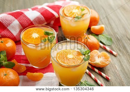 Tangerine cocktails with sliced mandarins, ice, mint with striped straws on a wooden table, close up
