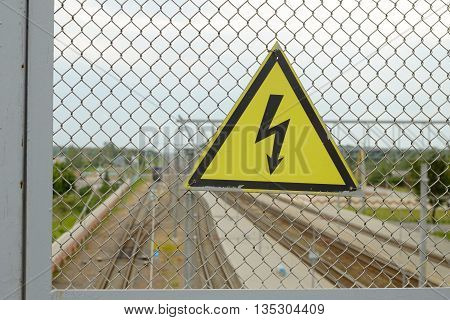 On the grid of the fence weighs sign. It warns of high voltage electricity.