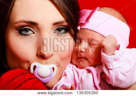 Parenting and love concept. Closeup funny mother with nipple in her mouth hugging one month old baby girl closeup portrait