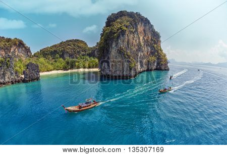 Aerial view of clear sea with traditional longtail thai boats and the rocky crag on the background
