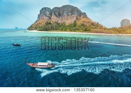 Aerial view of clear sea with traditional longtail thai boats and the rocky island of Koh Poda on the background