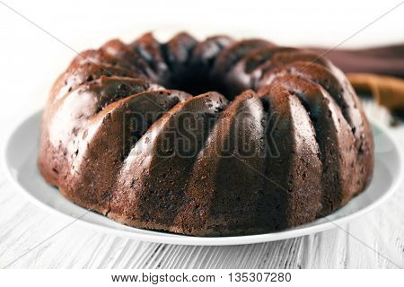 Chocolate cake on plate on white wooden background